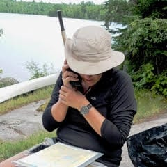 ​North Country client Sarah Hood using our satellite phone on day 3 of a Canadian fly-in canoe trip to change the van pick-up time. She also checked in at home to get an update about her young son.